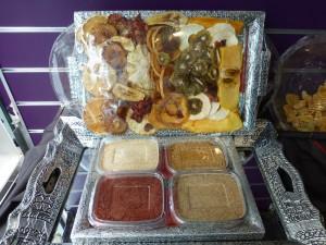 Background: tray of dried fruits  Foreground: powdered fruits - clockwise from upper left: orange, mango, lemon, strawberry
